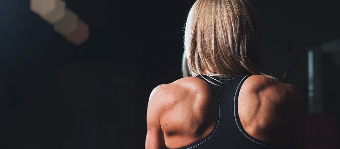 Kvinna med definierade muskler med ryggen vänd