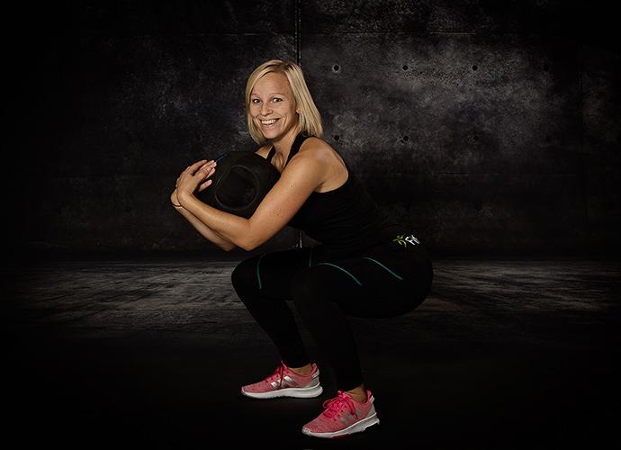 Kvinna som gör ett knäböj med en medicinboll