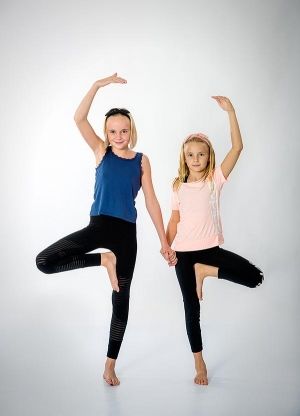 Två barn gör yogaställningar